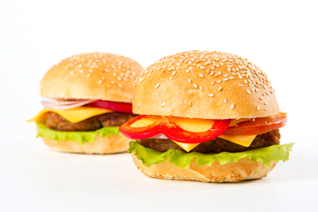 Two large burgers on a white background. Unhealthy food.