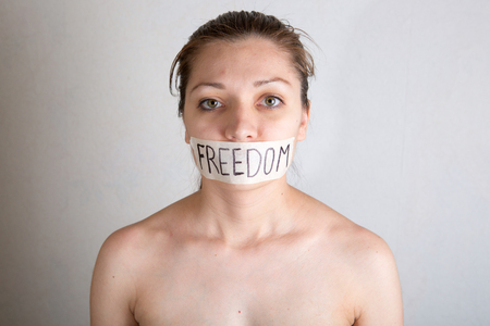 Woman with taped mouth with inscription word - freedom. Stock Photo