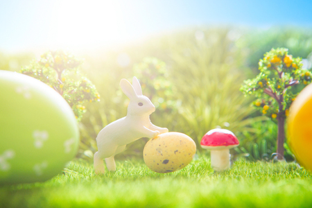Rabbit and easter eggs in green grass with blue sky. Stock Photo