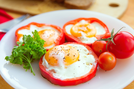 fried eggs in red peppers in a plate close-up. horizontal view from above Stock Photo