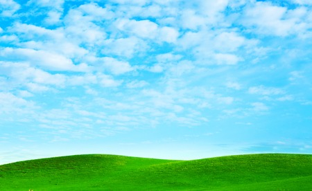 Green field on hills and blue sky. Natura landscape.