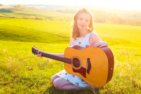 Young female left-handed musician playing guitar instrument at nature.