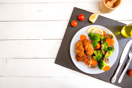 Chicken and Vegetables on a plate on black slate and white wooden table. Stock Photo