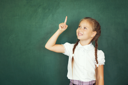 Smiling young little child girl in school on blackboard background. Education and school concept.