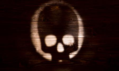 Silhouette human skull on dark wooden background.