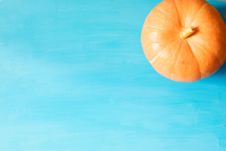 Pumpkin on blue wooden table. Halloween background with pumpkin. Copy space. Top view.