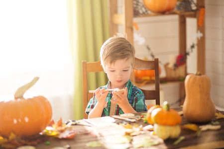 Happy Halloween concept. Cute little happy boy carving a pumpkin and decorated cookies for halloween on a table indoors. Archivio Fotografico