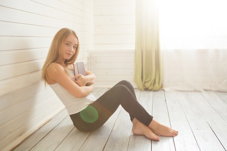 Student and education concept. Woman with book on the wooden white floor over window at home.