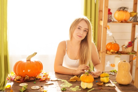 Ready to halloween invasion. Smiling young woman covering cookies and pumpkin in halloween decorated kitchen. Banco de Imagens