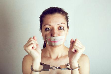 Malheureuse femme avec enveloppant sa bouche par du ruban adhésif peint un sourire.