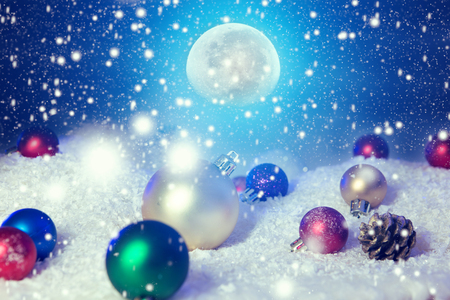 Snow christmas magic lights background. Christmas card with a winter forest and christmas decorations in a moonlit night.