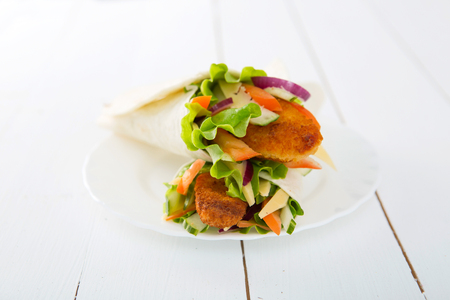 Rolls with vegetables and chicken in plat on wooden table