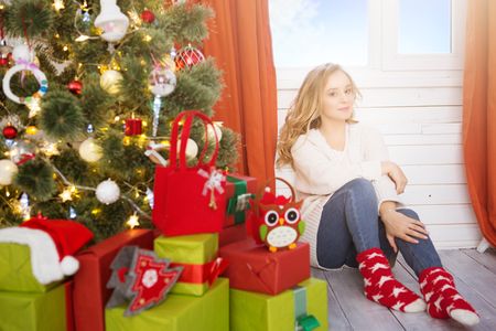 Young girl with christmas tree over window at home. Stock Photo