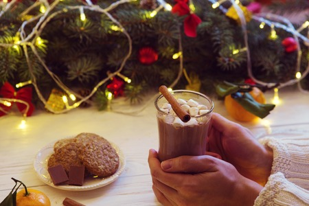 Woman hands ith cup of hot chocolate on christnas tree background. Standard-Bild - 114141369