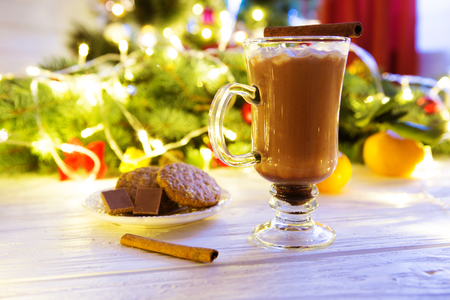 Hot drink with marshmallows on the background of Christmas decorations. Standard-Bild - 114141370