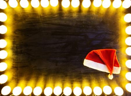 Christmas light on black background with santa hat. Standard-Bild - 114141373