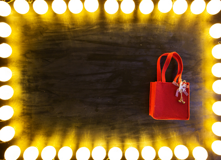 Christmas light on black background with red bag. Standard-Bild - 114141380