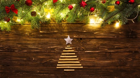 Christmas background with fir tree and decoration with Christmas tree for dry sticks on dark wooden board. Standard-Bild - 114141383