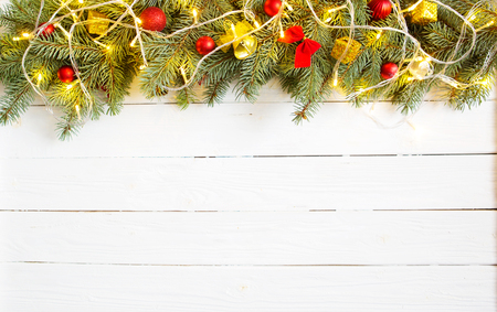 Christmas decoration and gift boxes on wooden background. Christmas or New Year background. Xmas decorations and fir branches, flat lay, blank space for a greeting text. Standard-Bild - 114141389