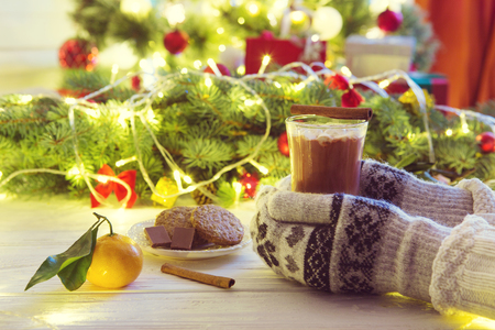 Hot chocolate with marshmallow in woman hand in mittens and sweater on a white wooden table against the background of the Christmas tree. Standard-Bild - 114141390
