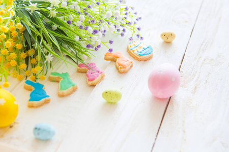 Colorful easter cookies on a white wooden background Фото со стока