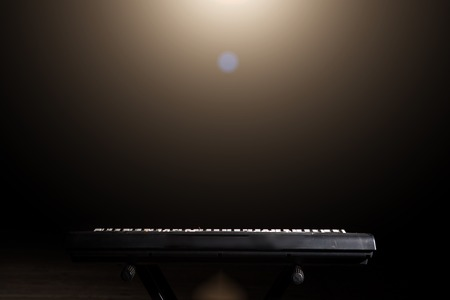 Synthesizer keyboard with a spotlight in the dark background with copy space.