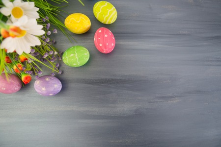 Colorful easter decoration with and flowers on a gray wooden table. Top view Фото со стока
