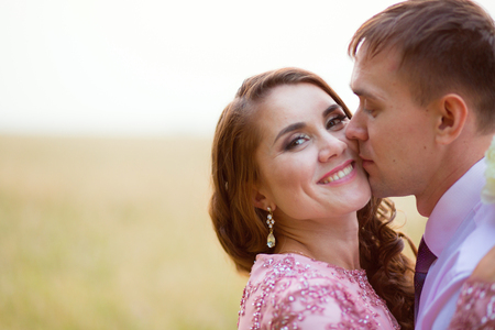 Young couple kissing in the summer field. Close-up.