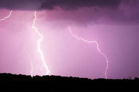 Lightning strike on the dark cloudy sky. Pink and purple and red toned image. 版權商用圖片