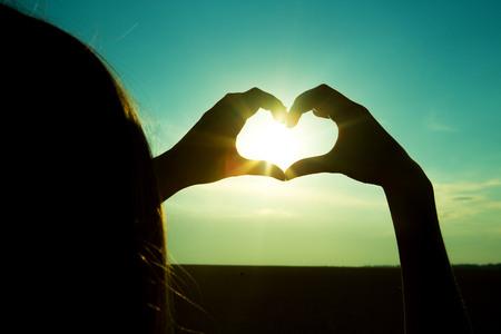 Girl holding a heart over sunset. Shape symbol with her hands and fingers