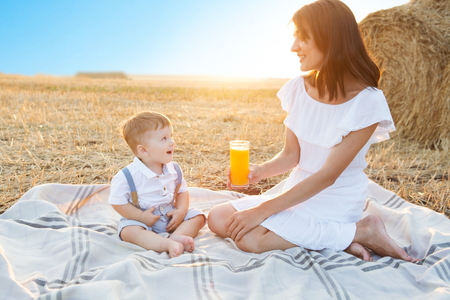 Mother and her son on holiday at a picnic. Mom is drinking orange juice. Happy family relaxing in nature. Healthy eating. Banco de Imagens