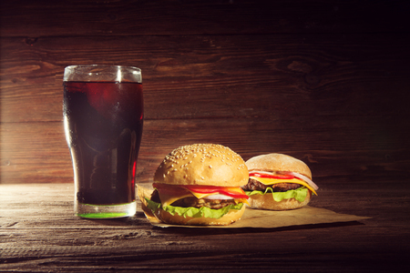 Two BBQ hamburgers with cola on wooden surface background. Фото со стока