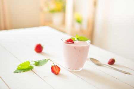 Yogurt with strawberry in glass on wooden rustic table in interior.
