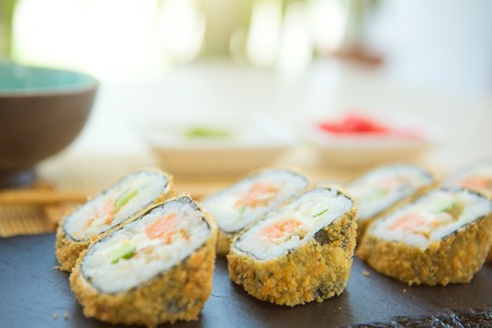 Tempura Maki Sushi - Deep Fried Roll made of Crab Meat, Paprika and Lettuce inside. Served on a Stone Plate 스톡 콘텐츠
