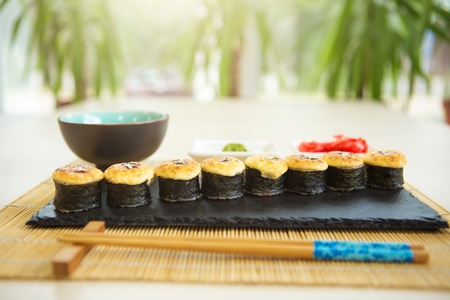 Sushi rolls with salmon and hot tea ceremony on a black wooden table. Fried hot Roll with salmon, avocado, cucumber.