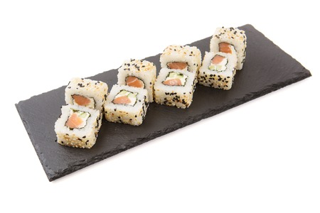Creative layout made of sushi. Flat lay. Food concept. Macro concept. Sushi isolated on shale food board on a white background