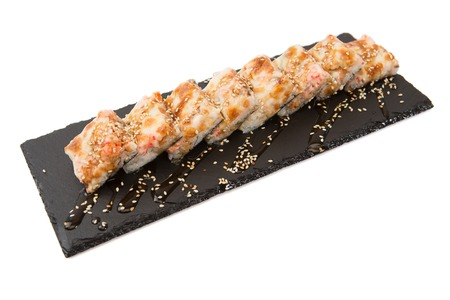Tempura Maki Sushi - Deep Fried Roll made of Fresh Raw Salmon, Avocado and Cream Cheese inside. Hot fried Sushi isolated on shale food board on a white background Stock Photo