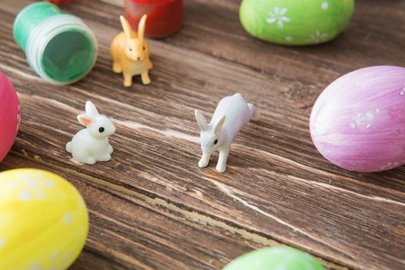 Easter eggs and Easter rabbits toys with flower on a wooden table.