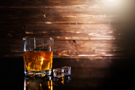 Glass of whiskey with ice cubes on a black table against wooden background Reklamní fotografie
