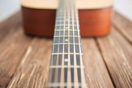 Close up of acoustic guitar with metal strings on a wooden table. Music concept.