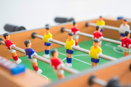 Table football game with yellow and red players and white goalkeeper. Table soccer game.