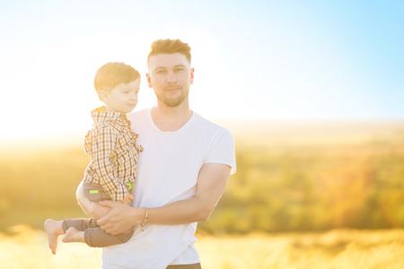 Szczęśliwy ojciec i syn razem w parku w ciepły słoneczny dzień. Koncepcja rodziny i miłości. Zdjęcie Seryjne