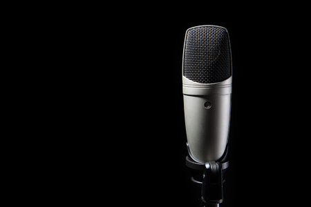 Professional condenser studio microphone on the black background with copy space on left