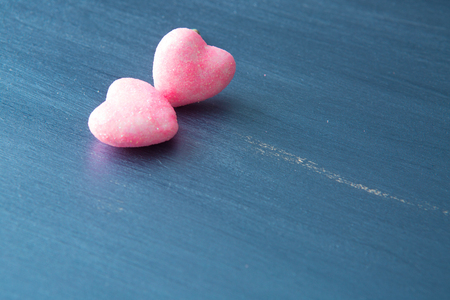 Two pink hearts on dark blue or silver on a wooden or metal background. Valentine's Day