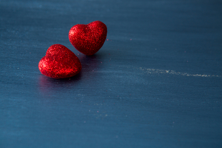 Two red hearts on dark blue or silver on a wooden or metal background. Valentine's Day