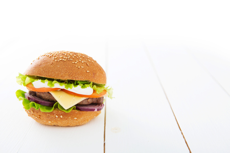 Tasty hamburger on the white wooden table.