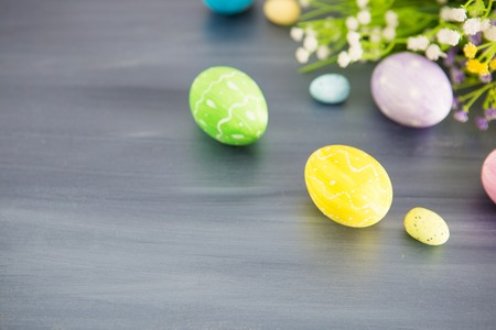 Painted easter decoration with and flowers on a gray wooden table.