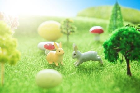 Jouets de lapin avec des oeufs de pâques sur une prairie. Prairie de printemps d'oeufs de pâques jaunes avec deux oeufs de lapin et de pâques. Conte de fée Banque d'images