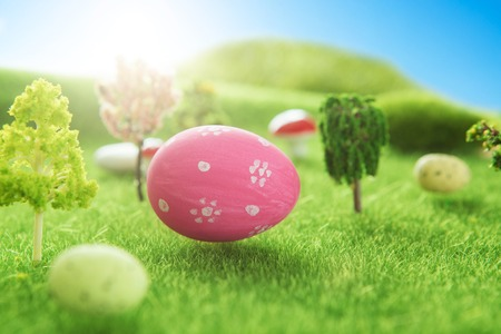 Easter background with pink Easter eggs on a green grass in pastel colors in spring of Dreamland or fairy world