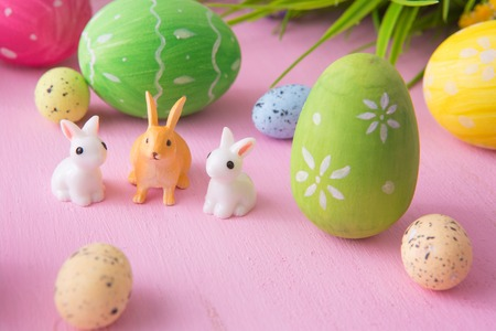 Composition with Easter eggs with rabbits or hare toys and flowers on a pink wooden background. 免版税图像